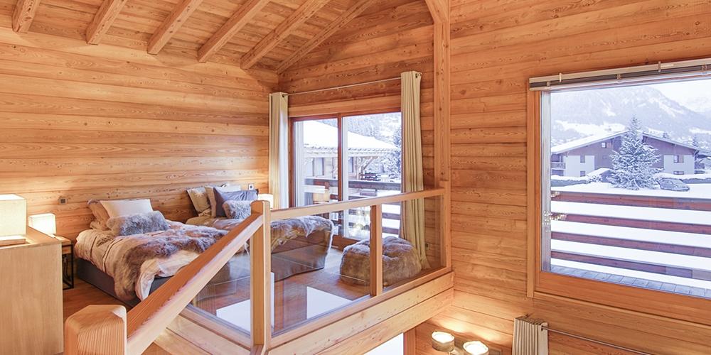Chambre mezzanine avec vue sur le salon et l'extérieur